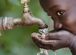 Kind trinkt aus Wasserhahn