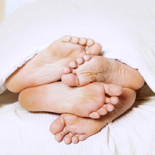 Füsse unter einer Bettdecke